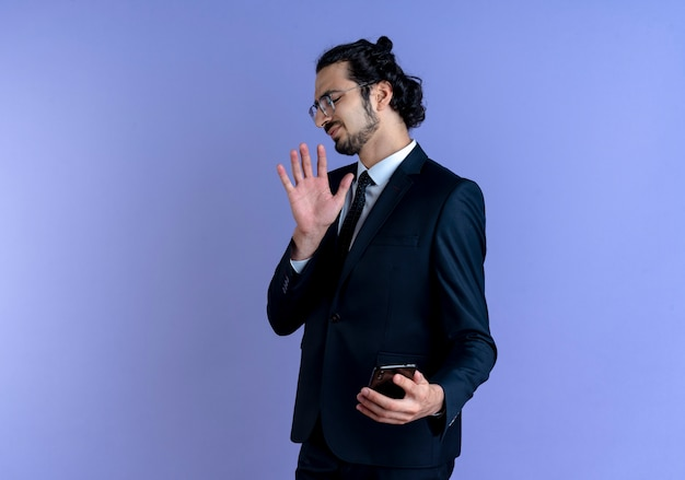Business man in black suit and glasses making defense gesture agains his smartphone with disgusted expression standing over blue wall