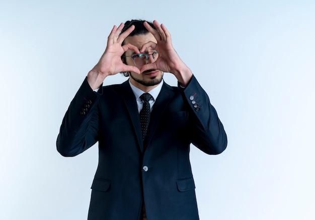 Uomo d'affari in abito nero e occhiali che fanno il gesto del cuore con le dita che guardano in avanti attraverso le dita in piedi sul muro bianco