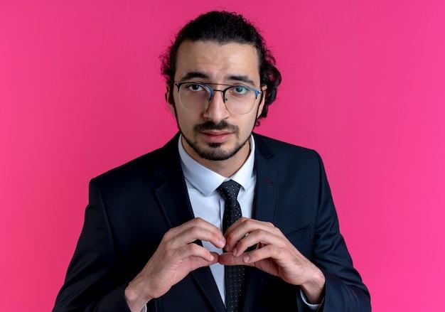 Uomo d'affari in abito nero e occhiali che fanno il gesto del cuore con le dita che guardano in avanti con espressione fiduciosa in piedi sul muro rosa