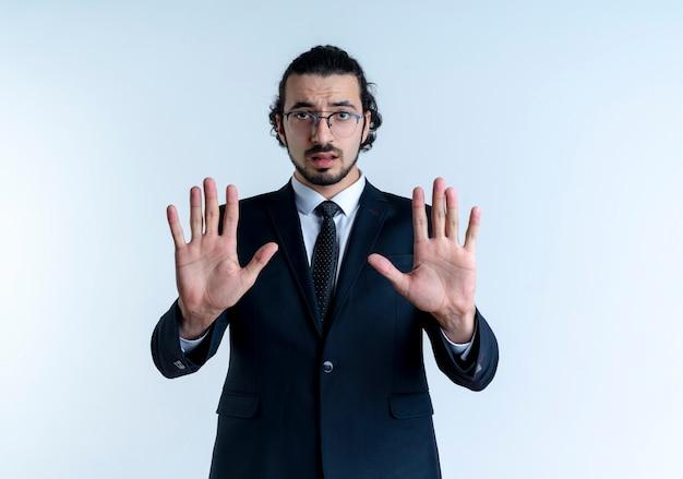 Uomo d'affari in abito nero e occhiali che fanno il segnale di stop con entrambe le mani guardando in avanti con la faccia seria in piedi sopra il muro bianco