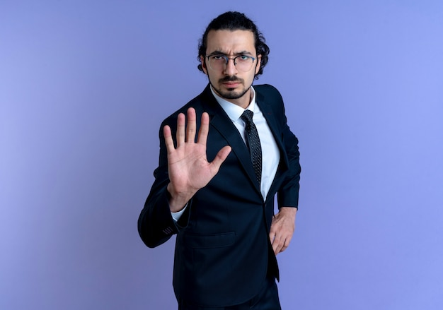 Uomo d'affari in abito nero e occhiali che fanno il segnale di stop con la mano che guarda in avanti con la faccia seria in piedi sopra la parete blu