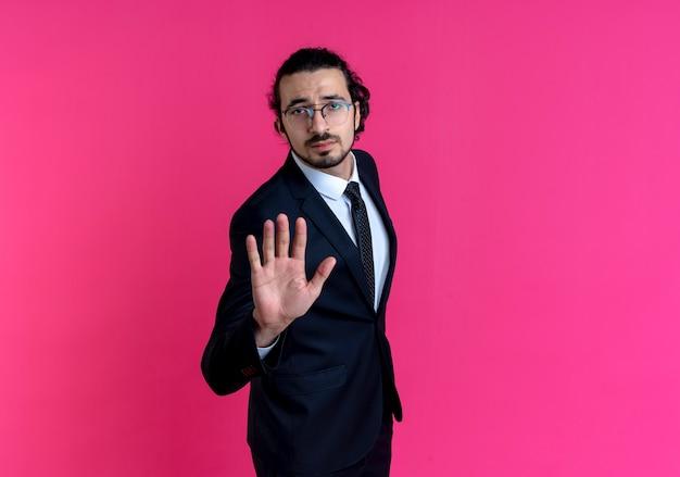 Uomo d'affari in abito nero e occhiali che fanno il segnale di stop con la mano che guarda in avanti con la faccia seria in piedi sul muro rosa