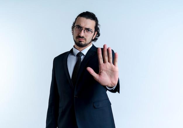Uomo d'affari in abito nero e occhiali che fanno il fanale di arresto con la mano aperta guardando in avanti con la faccia seria in piedi sopra il muro bianco