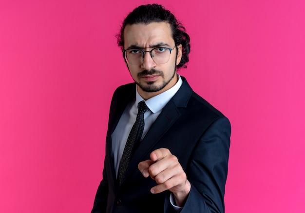 Uomo d'affari in abito nero e occhiali rivolti con il dito indice in avanti con la faccia seria in piedi sopra il muro rosa