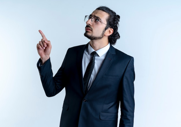 Uomo d'affari in abito nero e occhiali che punta con il dito indice in alto guardando fiducioso in piedi sopra il muro bianco