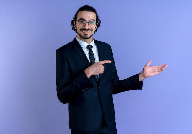 Uomo di affari in vestito nero e occhiali che presentano con il braccio della sua mano che indica con il dito al lato che sembra sorridente fiducioso in piedi sopra la parete blu