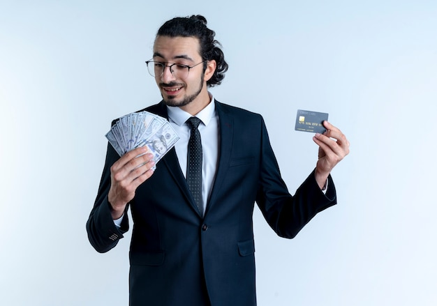 Business man in black suit and glasses showing cash and credit card smiling with happy face standing over white wall