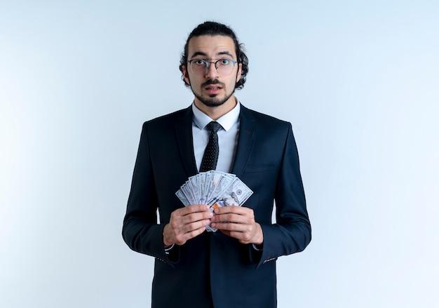 Uomo d'affari in abito nero e occhiali che mostrano denaro contante guardando in avanti confuso e molto ansioso in piedi sopra il muro bianco