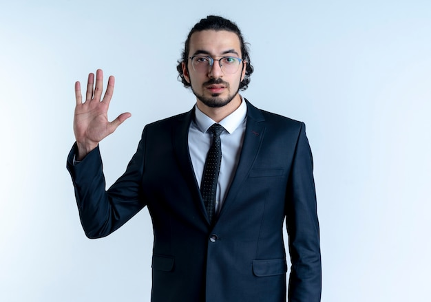 Uomo d'affari in abito nero e occhiali che mostra la mano aperta con la faccia seria in piedi sopra il muro bianco