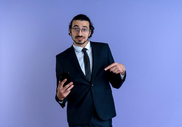 Business man in black suit and glasses showing smartphone pointing with finger to it smiling confident standing over blue wall 2