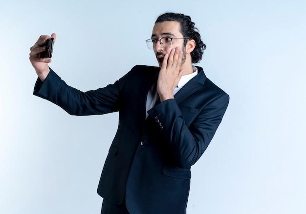 Uomo d'affari in abito nero e occhiali prendendo selfie utilizzando il suo telefono cellulare guardando sorpreso in piedi sopra il muro bianco