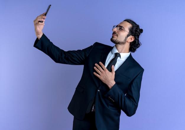 Uomo d'affari in abito nero e occhiali prendendo selfie utilizzando il suo smartphone cercando fiducioso in piedi oltre la parete blu