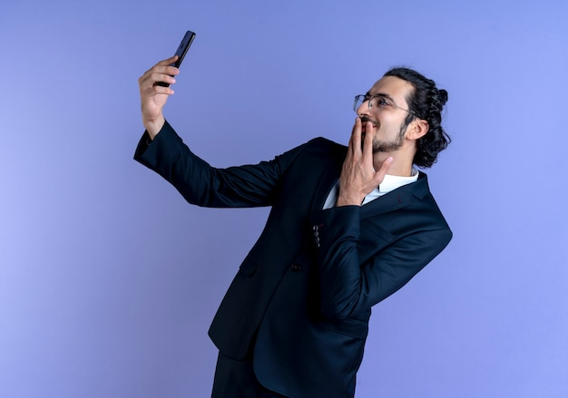 Uomo d'affari in abito nero e occhiali prendendo selfie utilizzando il suo smartphone guardando in avanti con un timido sorriso sul viso in piedi sopra la parete blu