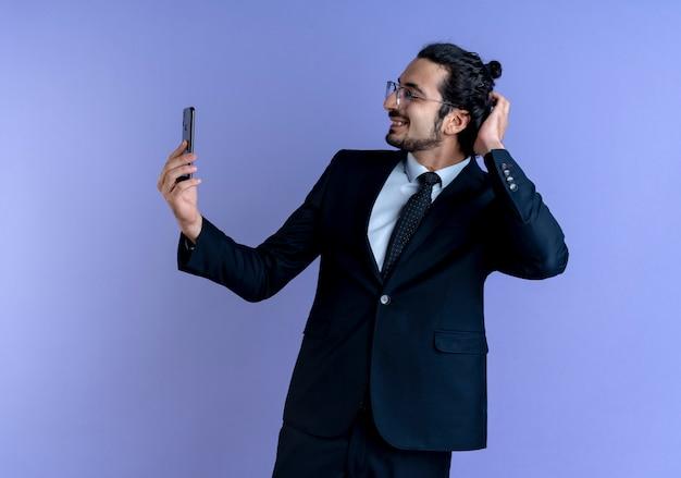 Uomo d'affari in abito nero e occhiali prendendo selfie utilizzando il suo smartphone sorridente con la faccia felice in piedi sopra la parete blu