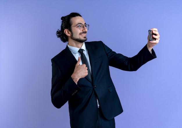 Uomo d'affari in abito nero e occhiali prendendo selfie utilizzando smartphone sorridente che mostra i pollici in su in piedi sopra la parete blu