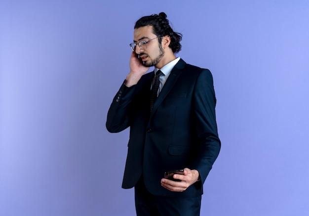 Uomo d'affari in abito nero e occhiali parlando al telefono cellulare cercando confuso in piedi sopra la parete blu