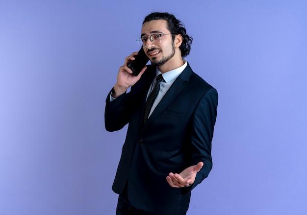 Uomo d'affari in abito nero e occhiali parlando al telefono cellulare cercando dispiaciuto in piedi sopra la parete blu