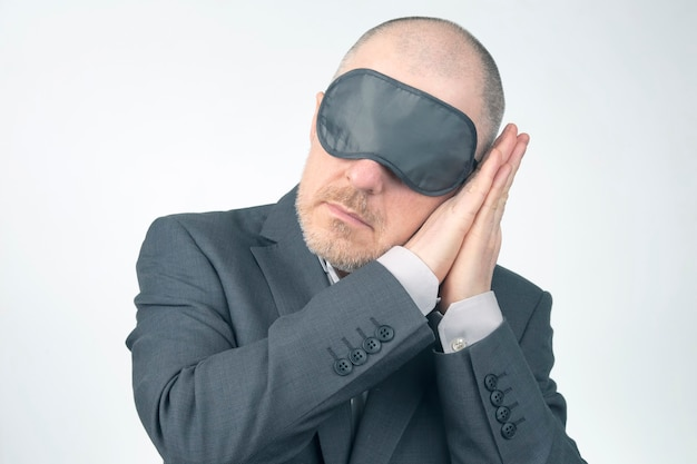 Business man in blindfold for sleeping with arms raised for rest on a white