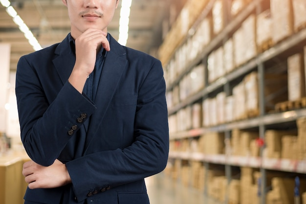 Business man in blue suit standing over warehouse background