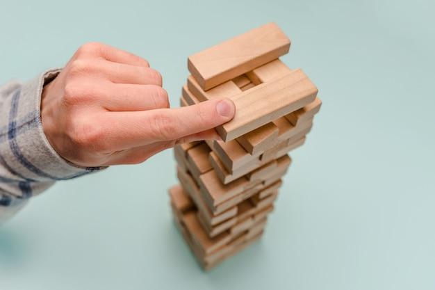 비즈니스 남자는 비즈니스 개발 및 계획의 상징으로 나무 블록 타워를 구축합니다.