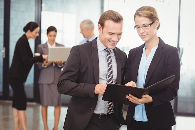Business man and business woman looking at file