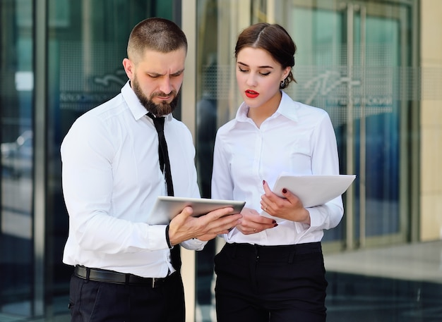 Business man and business woman in office business style talking and looking at the tablet  of an office building