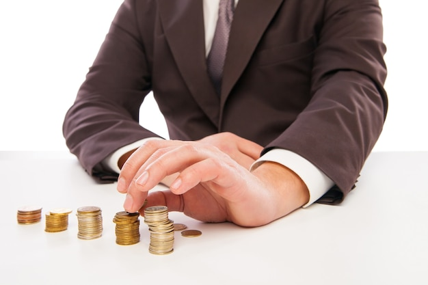 Business man calculating profit - closeup shot of hands counting coins isolated over white