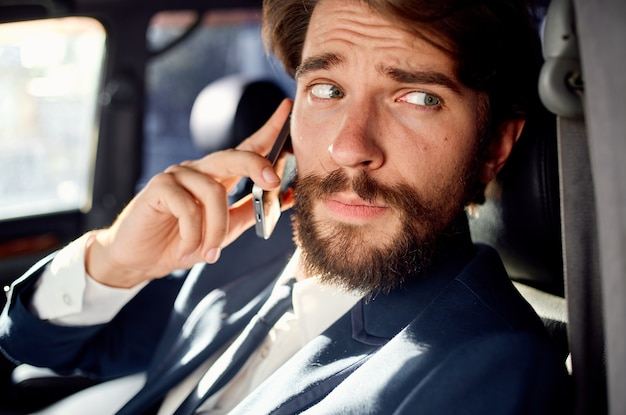 Business man in the car talking on the phone passenger. high quality photo