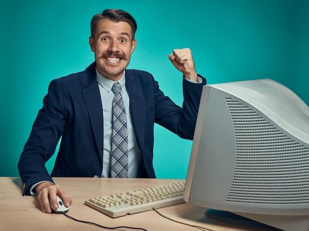 コンピューターの前の机に座って腕を上げて祝うビジネスマン