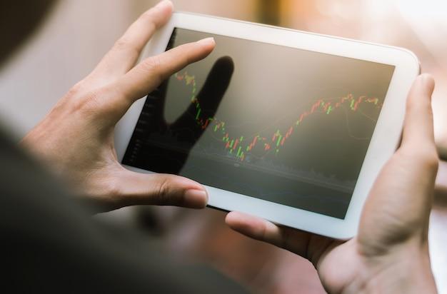 Деловой человек проверяет фондовый рынок на планшете