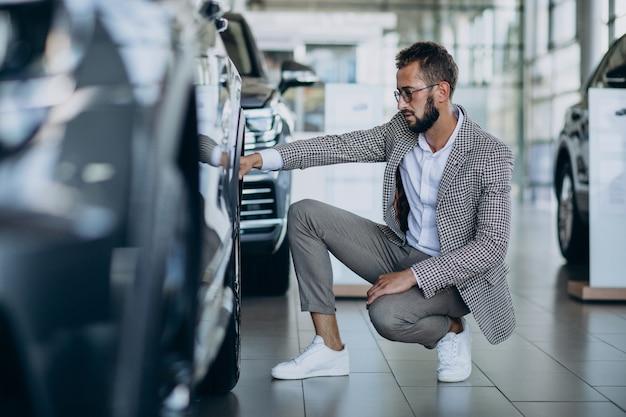 車のショールームで車を選ぶビジネスマン