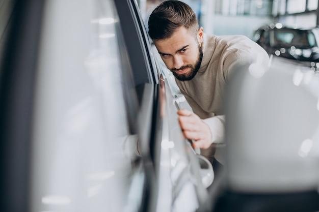 Uomo d'affari che sceglie un'auto in un salone di auto