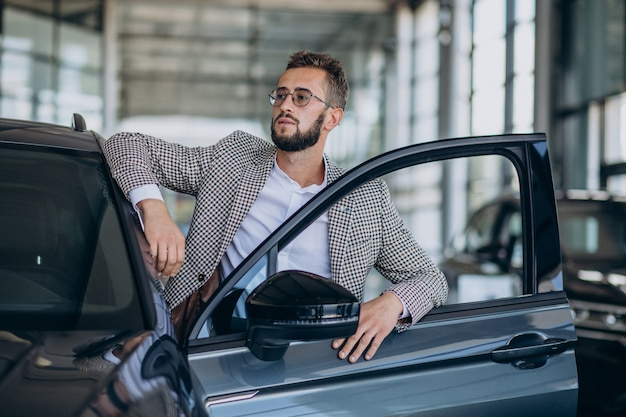 Uomo di affari che sceglie un'auto in uno showroom di auto