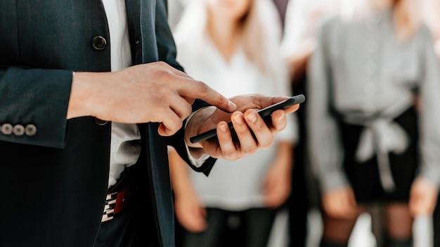 Деловой человек выбирает контакт на своем смартфоне