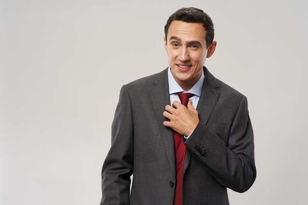 Business man in a classic suit straightens his tie around his neck and grins