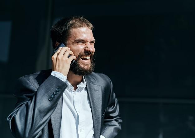 Деловой человек общается по телефону на открытом воздухе эмоции исполнительный менеджер образ жизни