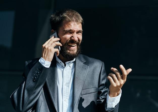 Деловой человек общается по телефону на открытом воздухе
