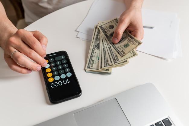 お金を数え、お金を節約し、将来のためにメモを取るビジネスマンそして家族の収入-費用、お金を節約するアイデア、そしてお金を数える