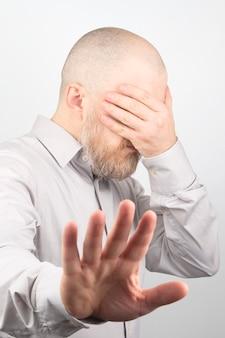 ビジネスマンは彼の手で彼の顔を覆った