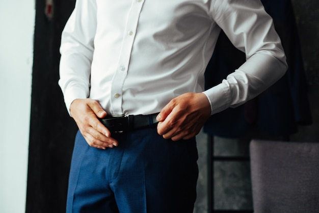 Business man in dark trousers and a white shirt fastened a black leather  belt close up. men's formal outfit. handsome guy  puts on suit