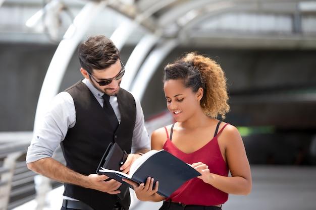 歩道橋の上に立っている間同僚と議論するビジネスの男性