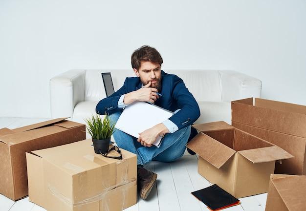 ビジネスマンは、オフィスマネージャーを開梱するもので箱を文書化します。