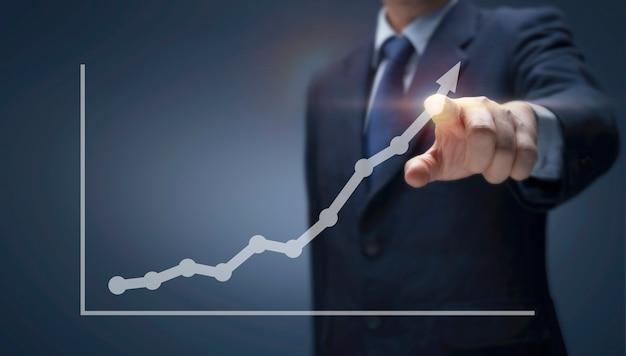 ビジネスマンは、高い成長率でレポートチャートを前に描きます。矢印グラフ上のビジネスマンポイントは、財務、販売利益、事業計画、株式市場への投資、経済成長の概念を示しています