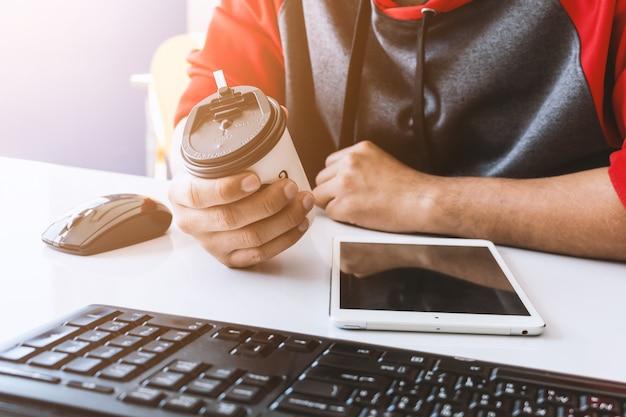 Деловой человек пьет кофе из одноразовой чашки в офисе
