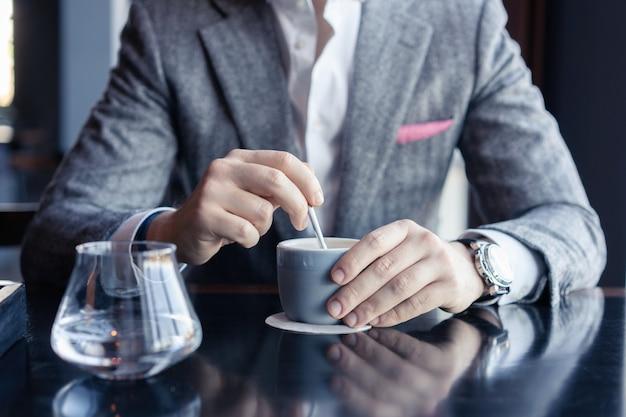 カフェでコーヒーを飲むビジネスマン。