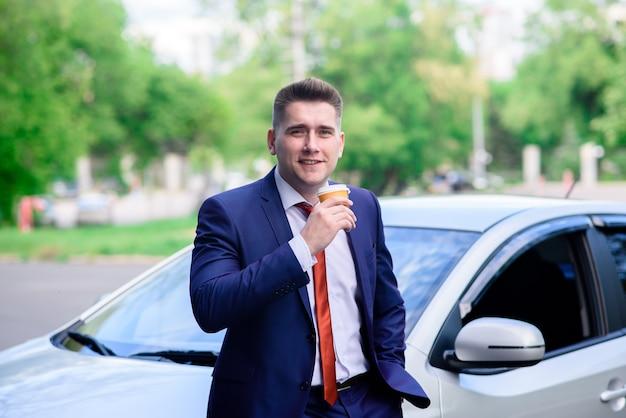 Деловой человек пьет кофе в машине.