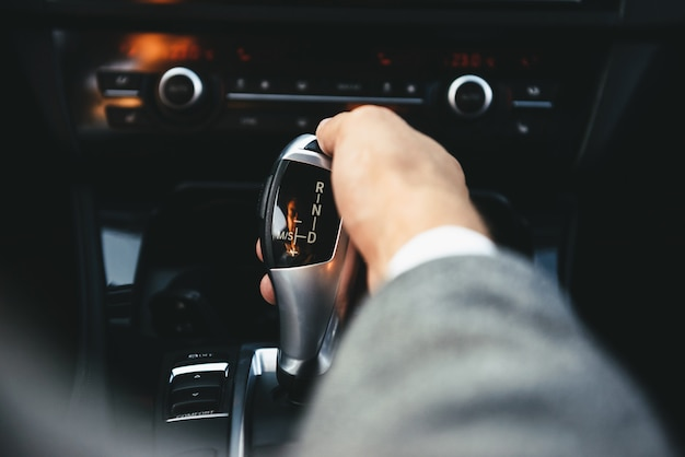 Business man driver hand shifting