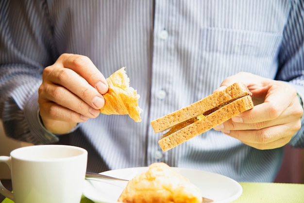 Business man eat the american breakfast set in a hotel