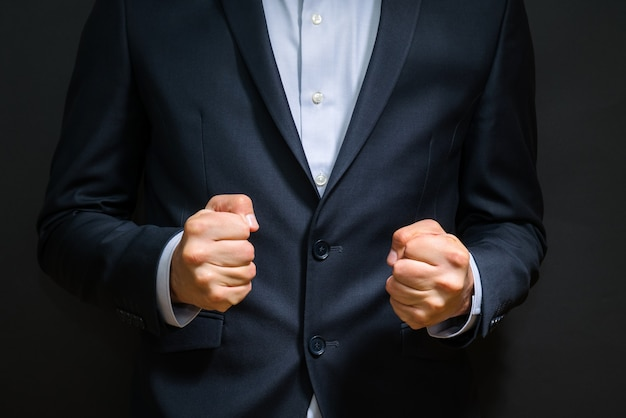 Business man fists clenched in anger - annoying emotions at work