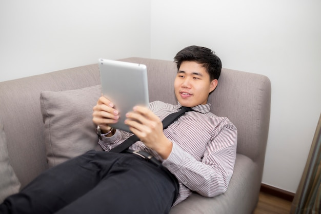 Business man in formal shirt playing tablet computer, watches new film, using free internet connection, enjoys conversation with friends in social networks and lying on safa at home.